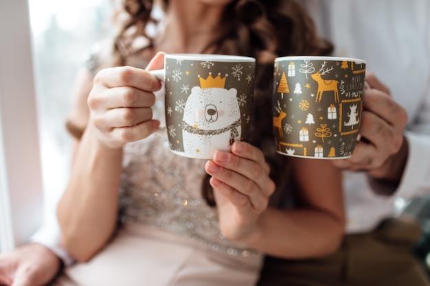Navidad. amor. casa. manos de hombre y mujer están sosteniendo con adornos navideños tazas con café o té caliente.