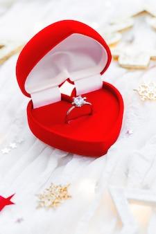 Navidad y año nuevo con adornos y anillo de compromiso de oro con diamante en caja de regalo.