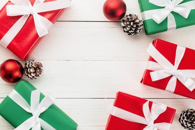 Navidad y año nuevo con cajas de regalo, bolas rojas y decoración de cono de pino de nieve en la vista superior de fondo de mesa de madera blanca con espacio de copia.