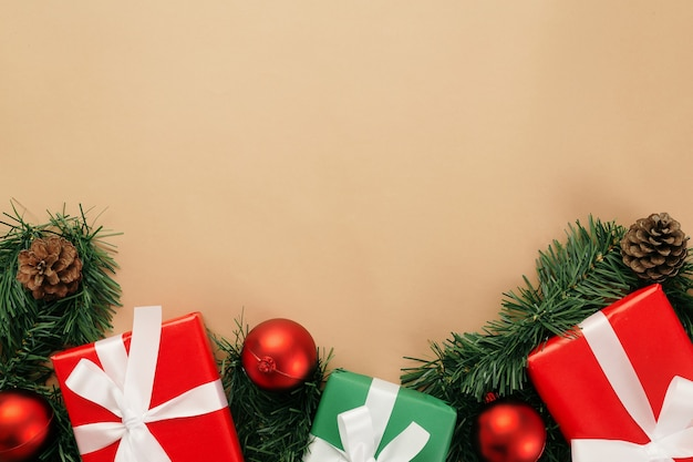 Navidad y año nuevo con cajas de regalo, bolas rojas y decoración de cono de pino en la vista superior de fondo beige con espacio de copia.