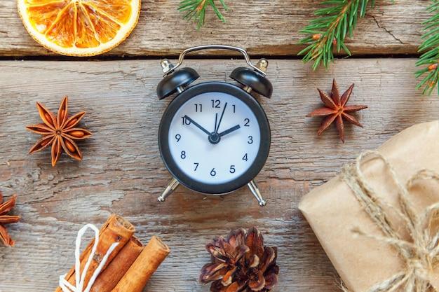 Navidad año nuevo composición objetos de invierno caja de regalo rama de abeto conos de pino palitos de canela reloj despertador sobre fondo de madera rústica en mal estado decoración de diciembre de vacaciones de navidad vista plana endecha