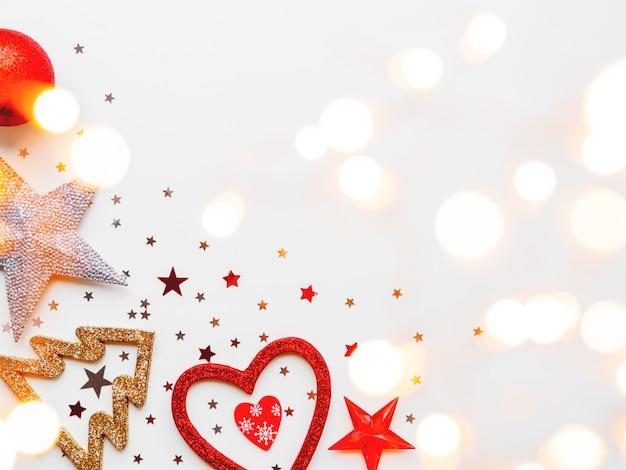 Navidad y año nuevo con decoraciones brillantes estrellas, bolas, copos de nieve, corazón, confeti y bombillas. .