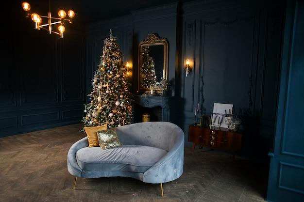 Navidad y año nuevo decorado habitación oscura interior. habitación decorada para vacaciones con chimenea, sofá azul claro y almohadas doradas. festiva noche de navidad con luces en el árbol con regalos