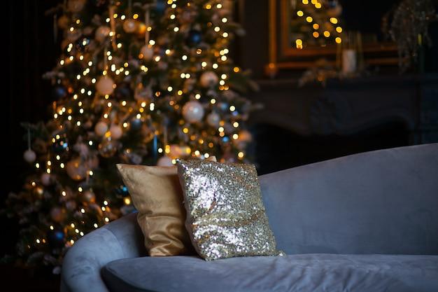 Navidad y año nuevo decorado habitación oscura interior. habitación decorada para vacaciones con sofá azul claro y almohadas doradas. festiva noche de navidad con luces en el árbol. noche romantica para dos