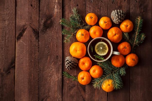 Navidad año nuevo con mandarinas, té y dulces en la mesa. invierno inmóvil. enfoque selectivo copyspace