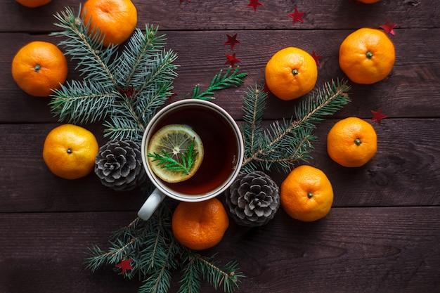 Navidad año nuevo con mandarinas, té y dulces en la mesa. invierno inmóvil. enfoque selectivo