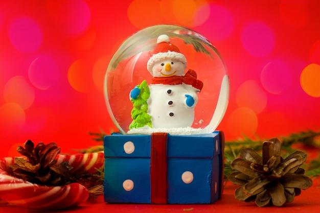 Navidad y año nuevo muñeco de nieve globo de nieve interior sobre fondo rojo bokeh