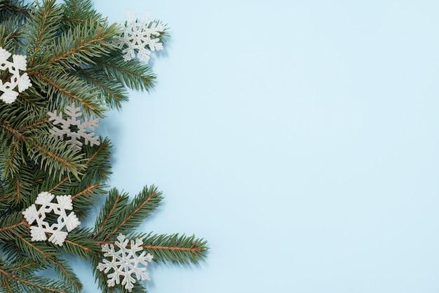 Navidad. árbol verde y copos de nieve decoraciones sobre fondo azul. vista superior con copycopyspace.