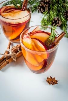 Navidad, bebidas de acción de gracias. otoño, cóctel de invierno, sangría caliente, vino caliente con especias, manzana, romero, canela, anís. sobre mesa de mármol blanco. con conos, romero. copia espacio
