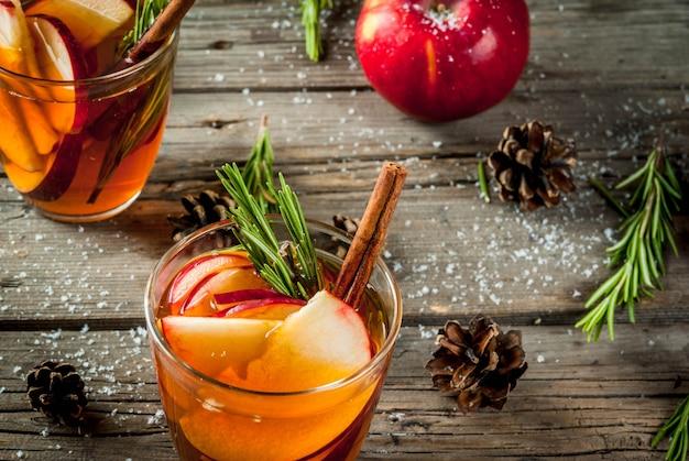 Navidad, bebidas de acción de gracias. otoño, cóctel de invierno, sangría caliente, vino caliente con especias, manzana, romero, canela, anís. en la vieja mesa de madera rústica. con conos, ramas de romero. copia espacio