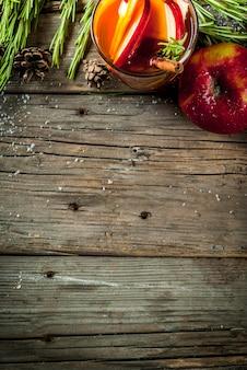 Navidad, bebidas de acción de gracias. otoño, cóctel de invierno, sangría caliente, vino caliente con especias, manzana, romero, canela, anís. en la vieja mesa de madera rústica. con conos, romero. copia espacio vista superior