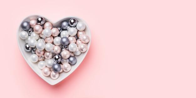 Navidad blanca, rosa, bolas grises en forma de corazón en rosa. vista superior. banner de navidad .