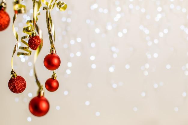 Navidad con bolas rojas colgantes y cinta de oro en un bonito bokeh.
