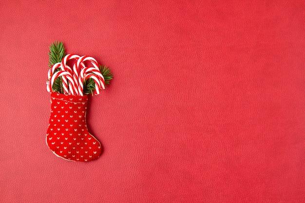 Navidad cañas de azúcar en medias rojas. invitación, celebración de navidad, concepto de tarjeta de felicitación festiva