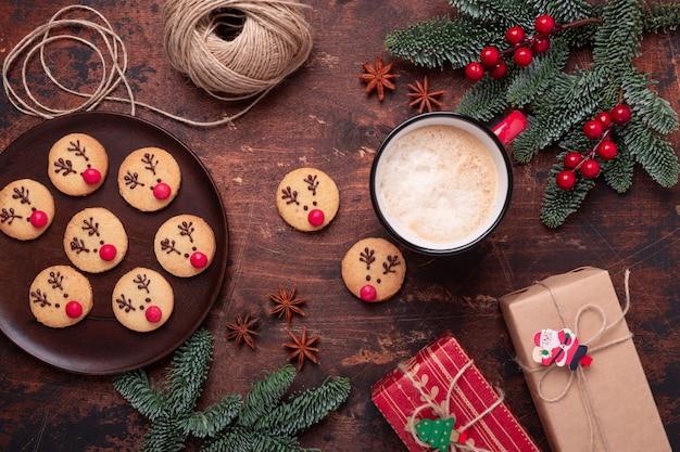 Navidad con chocolate caliente, galletas caseras, ramas de abeto y regalos.