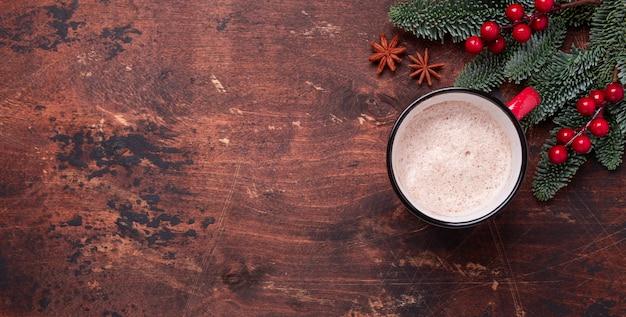 Navidad con chocolate caliente, ramas de abeto y acebo.