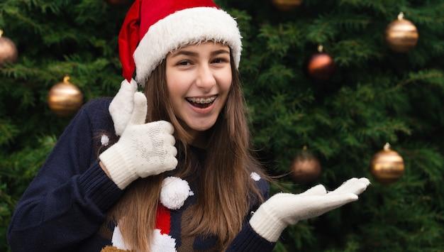 Navidad como un pulgar hacia arriba. close up retrato de mujer con un sombrero de santa claus con emoción. en el contexto de un árbol de navidad.