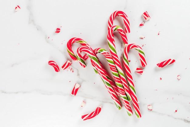 Navidad, concepto de invierno. fiestas, dulces, golosinas. bastón de caramelo tradicional en forma de ramo, entero y roto en pedazos. mesa de mármol blanco, vista superior, copyspace