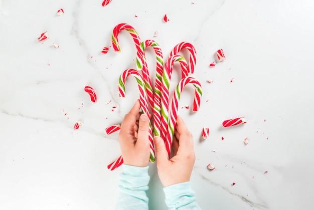 Navidad, concepto de invierno. fiestas, dulces, golosinas. manos de niña sosteniendo el bastón de caramelo tradicional en forma de ramo, entero y roto en pedazos. mesa de mármol blanco, vista superior, copyspace