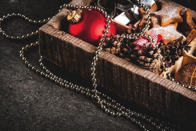 Navidad, decoración navideña. bolas de árboles de navidad, guirnaldas, estrellas de pan de jengibre, molde de galletas, arcos para regalos, conos de abeto en caja de madera sobre mesa de piedra negra, vista superior