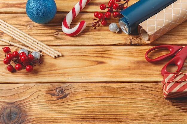 Navidad envolviendo y decorando artículos sobre fondo de madera con espacio de copia