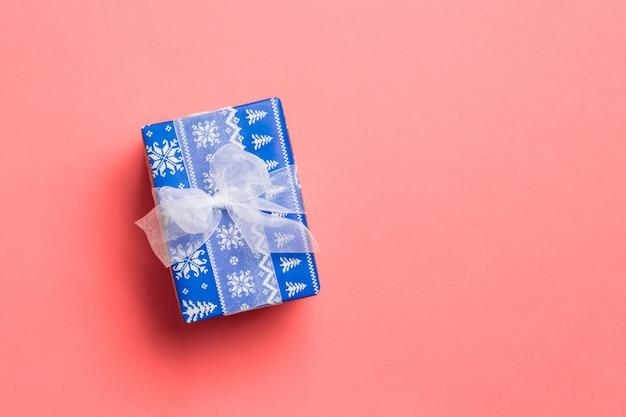 Navidad envuelta u otro regalo hecho a mano en papel con cinta blanca sobre fondo coral vivo