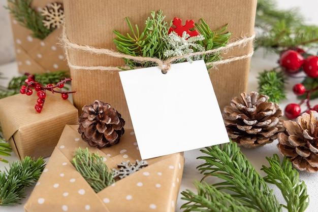 Navidad envuelto presente con etiqueta de regalo de papel cuadrado sobre una mesa blanca con ramas de abeto y decoraciones de cerca. composición de invierno rústico con maqueta de etiqueta de regalo en blanco, espacio de copia