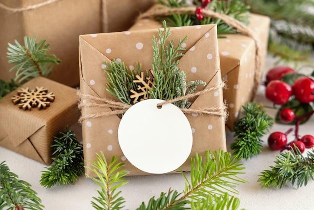 Navidad envuelto presente con etiqueta de regalo de papel redondo sobre una mesa blanca con ramas de abeto y decoraciones de cerca. composición de invierno rústico con maqueta de etiqueta de regalo en blanco, espacio de copia