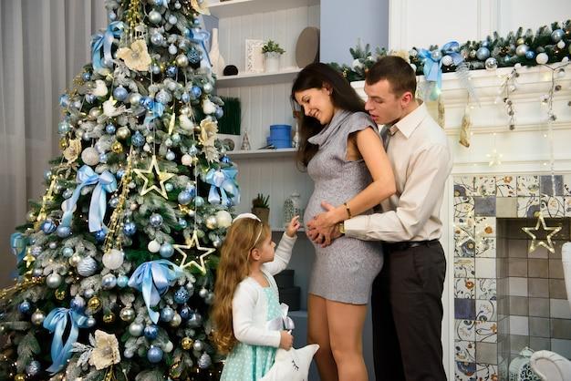 Navidad familia de pie cerca del árbol de navidad