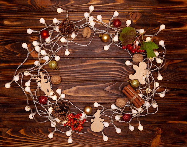 Navidad y feliz año nuevo en el fondo de vacaciones con conos naturales, nueces, juguetes de madera. tarjeta de navidad, bokeh, chispas, brillando. concepto de vacaciones de invierno. endecha plana, vista superior