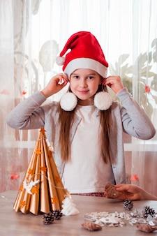 Navidad hecho a mano. la niña se prueba las decoraciones del árbol de navidad como aretes. vista vertical