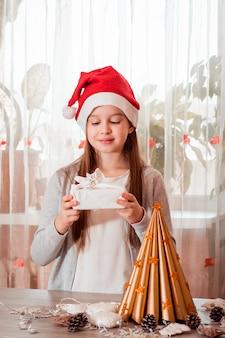 Navidad hecho a mano. una niña sosteniendo un regalo ecológico furoshiki en sus manos. cero desperdicio