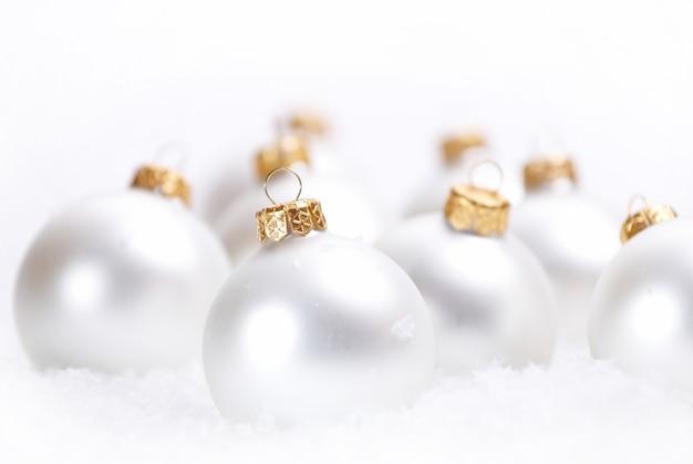 Navidad hermosas bolas blancas con nieve sobre fondo blanco.