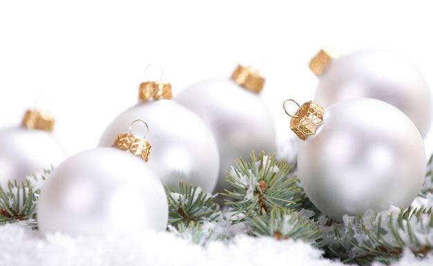 Navidad hermosas bolas blancas con rama de abeto y nieve sobre fondo blanco.