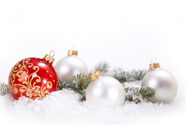 Navidad hermosas bolas blancas y rojas con rama de abeto y nieve sobre fondo blanco.