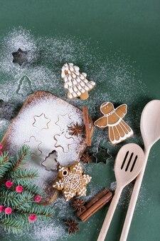 Navidad para hornear. abetos con moldes de decoración, harina, especias y galletas en una tabla de cortar.