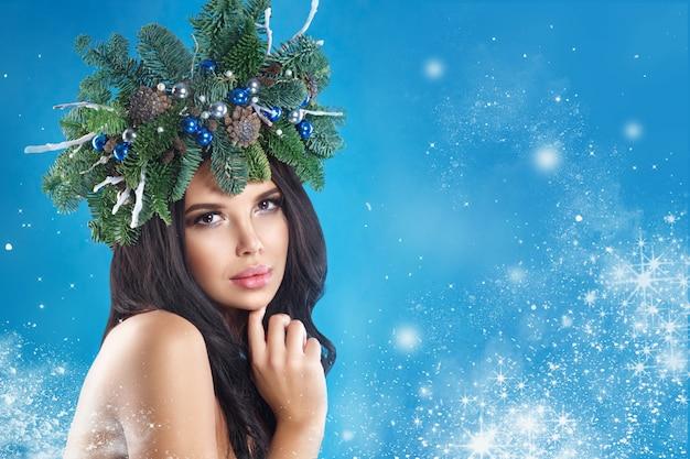 Navidad invierno mujer. hermoso año nuevo y árbol de navidad vacaciones peinado y maquillaje.