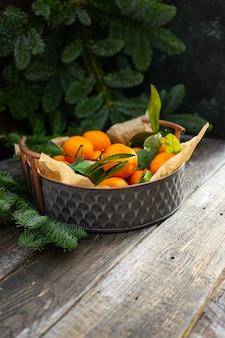 Navidad mandarina vintage cobre cuenco y ramas de abeto.