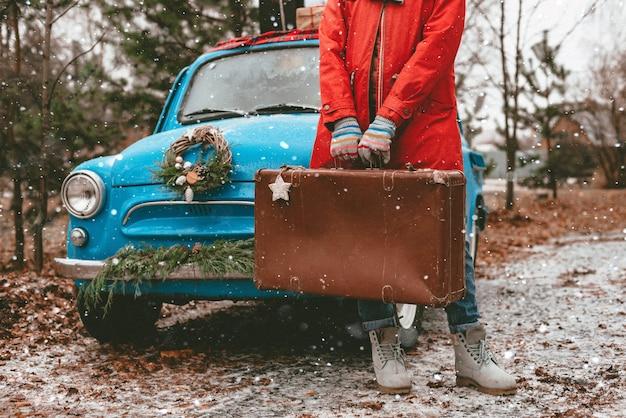 Navidad maqueta en una vieja maleta en manos de una mujer abrigo rojo. coche retro azul decorado corona de navidad coníferas. nochevieja 2021.