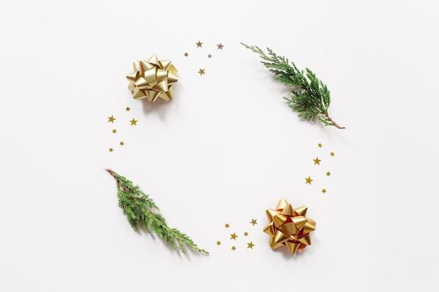 Navidad de moda, composición de año nuevo. ramas de abeto, adornos dorados sobre fondo beige.