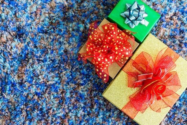 Navidad muchos regalos en la alfombra azul interior de la vista superior, decoración durante navidad y año nuevo.