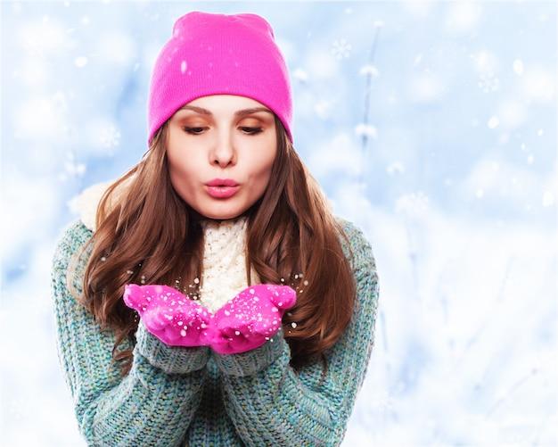 Navidad niña mujer de invierno soplando nieve