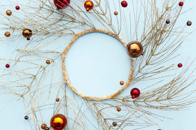 Navidad o año nuevo composición de invierno. marco redondo hecho de ramas de árboles dorados y adornos decorativos de navidad.