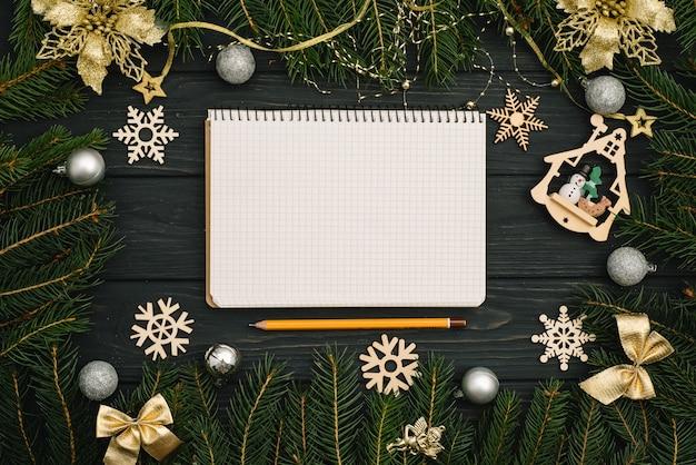 Navidad o año nuevo fondo de madera oscura, pizarra de navidad enmarcada con adornos de temporada, vista desde arriba