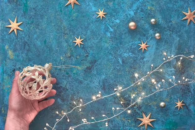 Navidad o año nuevo plano pone pared en tablero con textura de azulejo oscuro. vista superior plana en guirnalda de navidad, adornos dorados y estrellas. mano que sostiene la baratija adornada. ¡feliz navidad y un feliz año nuevo!