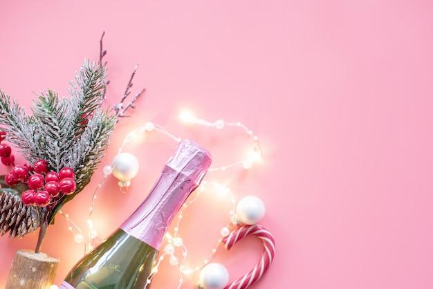 Navidad plana pone con champán y guirnaldas sobre fondo rosa. fondo de navidad y año nuevo.
