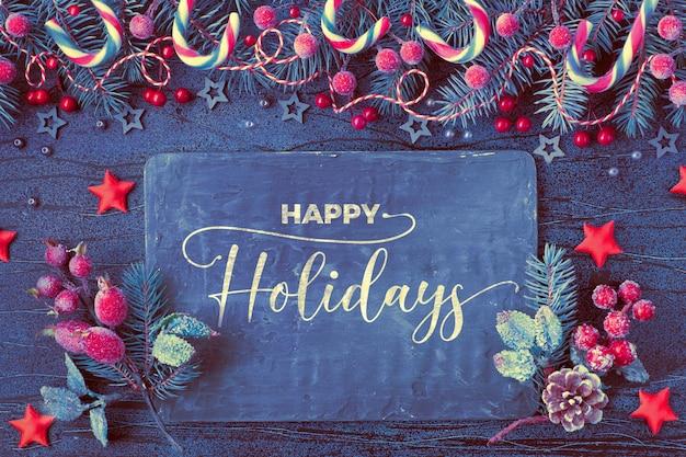 Navidad con ramas de abeto, bayas rojas y bastones de caramelo con tablero negro sobre fondo azul oscuro con textura, texto