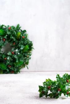 Navidad simple con acebo, hojas de ilex y pequeñas frutas rojas en piedra