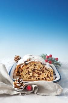 Navidad stollen en superficie festiva blanco-azul con ramas de abeto y bayas, espacio de texto