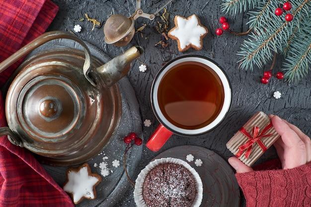 Navidad con té, dulces y mano femenina sosteniendo una pequeña caja de regalo